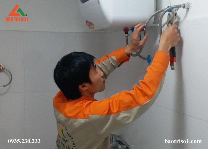 Hình ảnh kỹ thuật Bảo Trì đứng tháo bình ra để tiến hành vệ sinh trực tiếp tại nhà