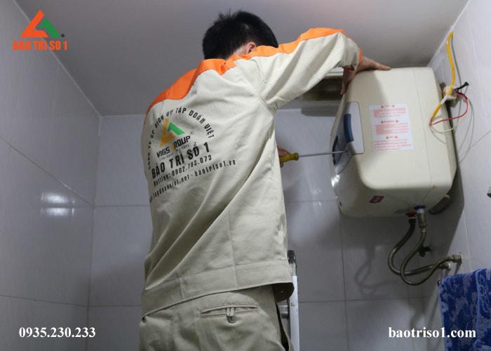 Hình ảnh kỹ thuật đang đứng để tháo bình nóng lạnh để vệ sinh ngay tại nhà