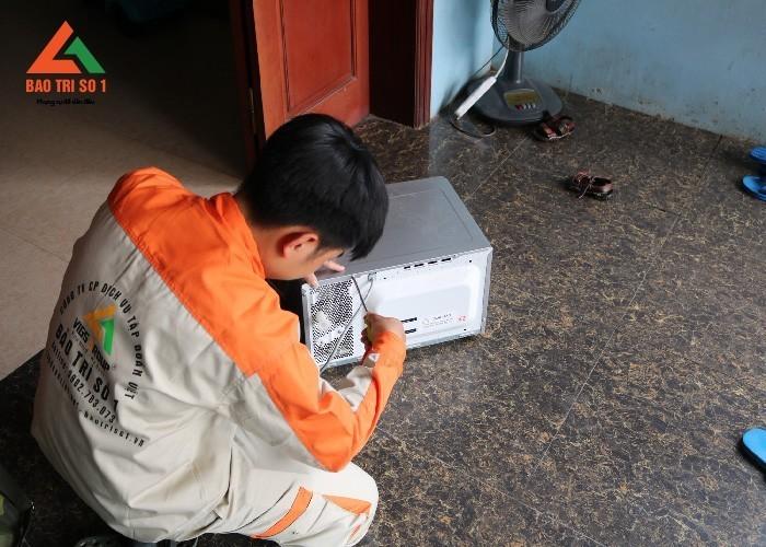 Hình ảnh kỹ thuật viên đang sửa lò vi sóng tại nhà khách hàng ở quận Thanh Xuân
