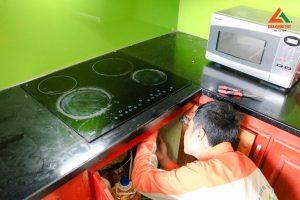 Nhân viên kỹ thuật tiến hành kiểm tra lỗi và cách khắc phục để sửa chữa bếp từ tại nhà của khách hàng